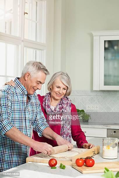 Germany, Berlin, Man and woman preparing food, smiling