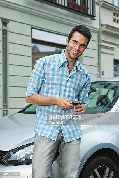 Germany, Berlin, Man using cell phone in front of car