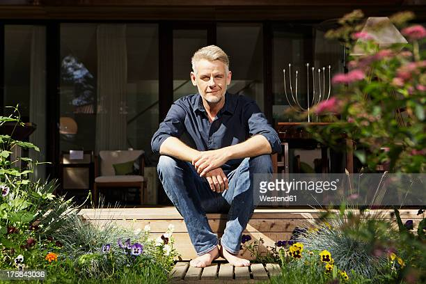 Germany, Berlin, Mature man relaxing on terrace, smiling, portrait