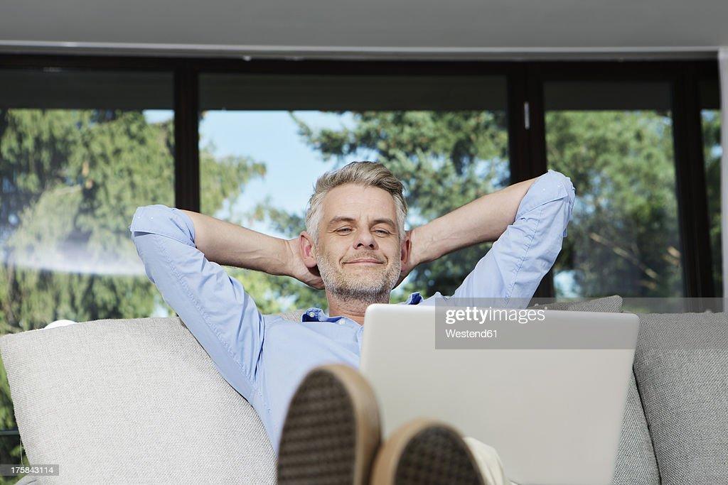 Germany, Berlin, Mature man sitting on sofa using laptop