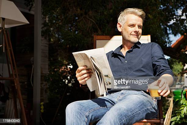 Germany, Berlin, Mature man sitting on terrace and reading newspaper