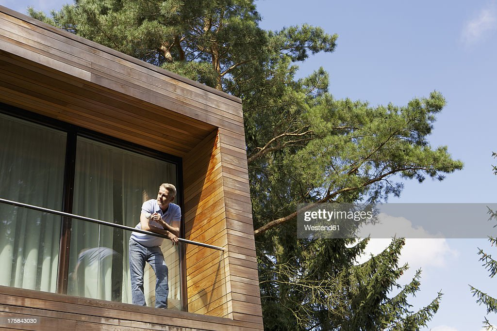 Germany, Berlin, Mature man standing on balcony and relaxing : Stock Photo