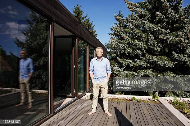 Germany, Berlin, Mature man standing on terrace, portrait