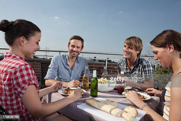 Germany, Berlin, Men and women at barbecue on roof terrace, smiling