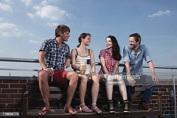 Germany, Berlin, Men and women sitting on roof terrace, smiling