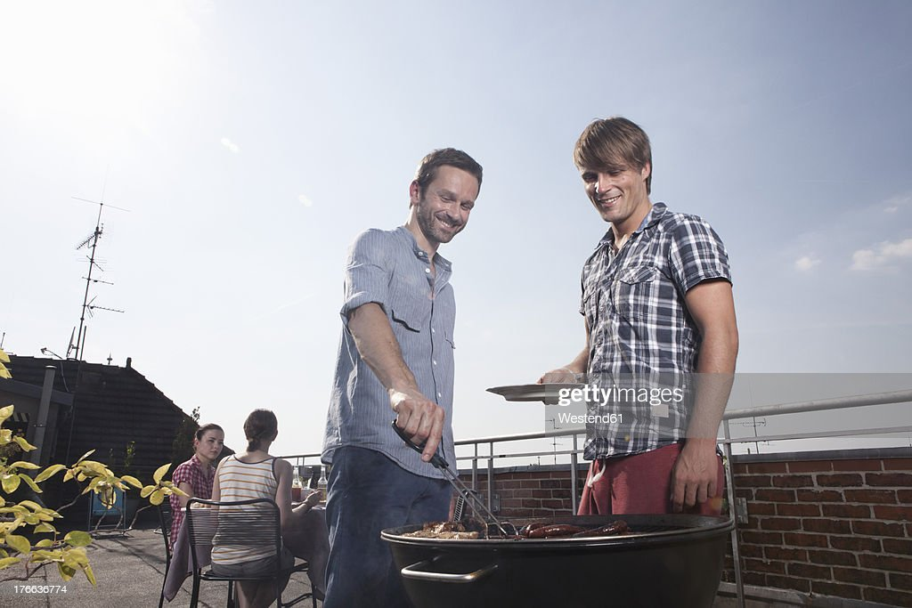 Germany, Berlin, Men barbecueing on grill, smiling