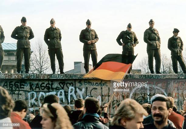 Germany Berlin morning of the November 11th after the fall of the Berlin Wall GDR mil border guards on the wall at Brandenburg Gate looking down to...