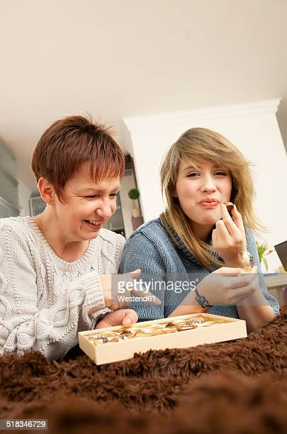 Germany, Berlin, Mother and daughter eating chocolates