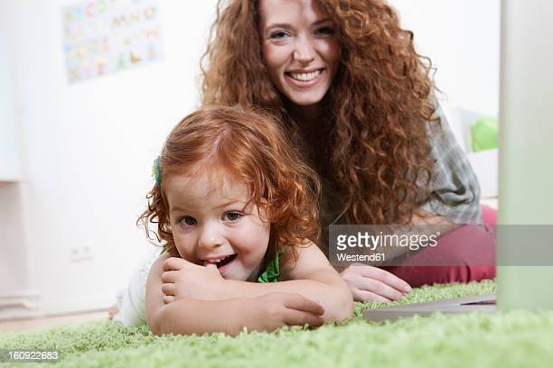 Germany, Berlin, Mother and daughter relaxing on floor