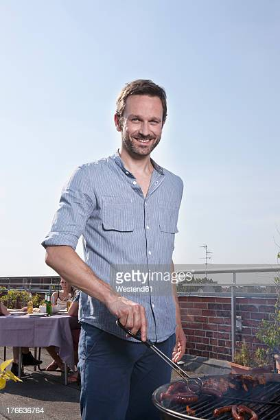 Germany, Berlin, Portrait of man barbecueing on grill, smiling