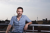 Germany, Berlin, Portrait of man on roof terrace, smiling