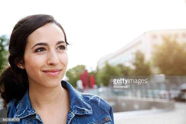 Germany, Berlin, portrait of smiling young woman on city trip