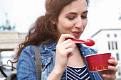 Germany, Berlin, portrait of young female tourist eating ice cream near Brandenburg Gate
