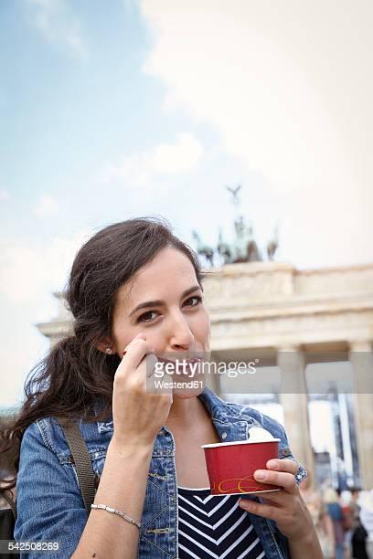 Germany, Berlin, portrait of young female tourist eating ice cream near Brandenburg Gate