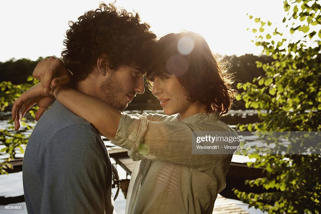 Germany, Berlin, River Spree, Young couple embracing by river, side view : Stock Photo