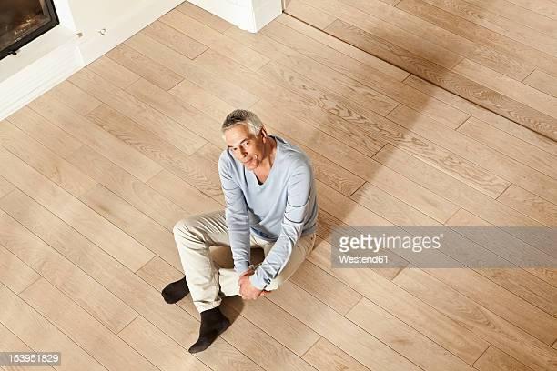 Germany, Berlin, Senior man sitting on floor, portrait