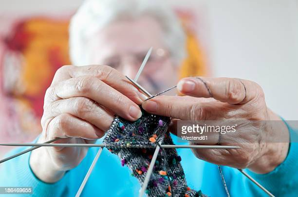 Germany, Berlin, Senior woman knitting socks, close up