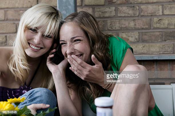 Germany, Berlin, Two women using mobile phone, messing about