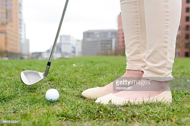Germany, Berlin, Young businesswoman playing golf