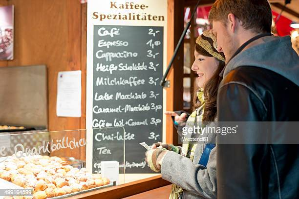 Germany, Berlin, young couple buying deep-fried pastries at Christmas market