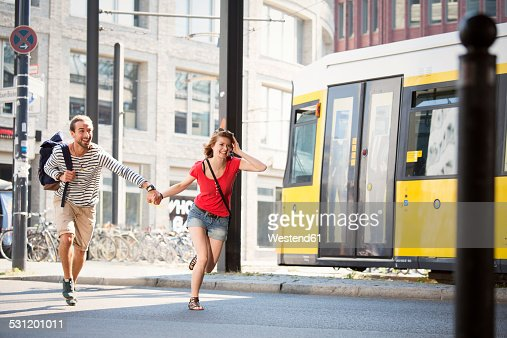 Germany, Berlin, Young couple running in street