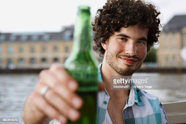 Germany, Berlin, Young man holding beer bottle, smiling, portrait
