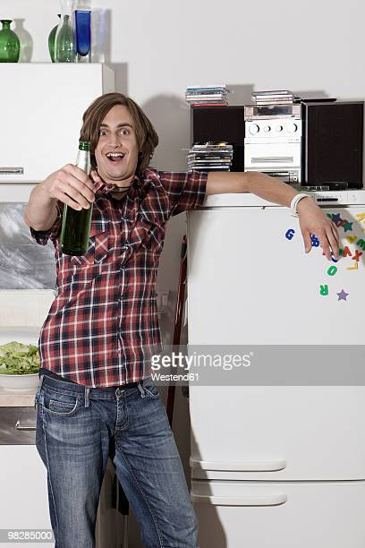 Germany, Berlin, Young man standing by refrigerator holding beer bottle, portrait
