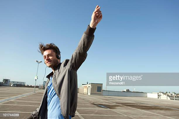 Germany, Berlin, Young man on empty parking level wearing headphones