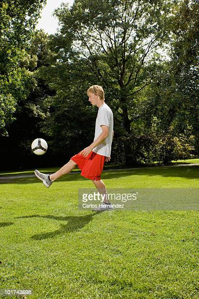 Germany, Berlin, Young man on lawn playing with soccer ball