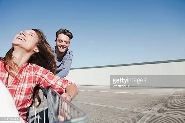 Germany, Berlin, Young man pushing young woman in shopping cart