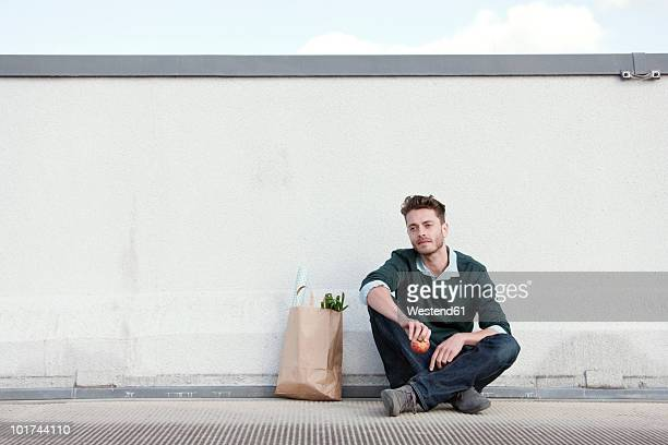 Germany, Berlin, Young man sitting in front of wall, holding an apple, portrait