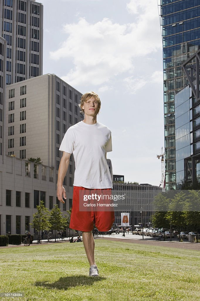 Germany, Berlin, Young man stretching leg on lawn : Stock Photo