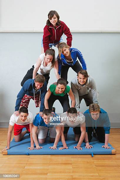 Germany, Berlin, Young people and teenager building human pyramid