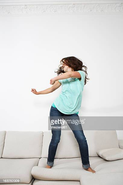 Germany, Berlin, Young woman dancing on couch