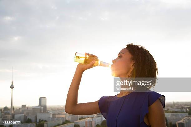 Germany, Berlin, Young woman drinking beer