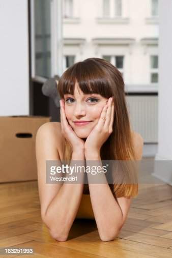 Germany, Berlin, Young woman lying on floor, smiling