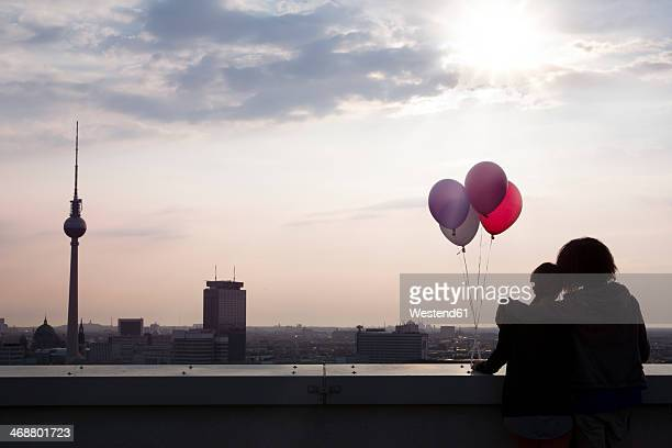 Germany, Berlin, Young woman on rooftop terrace