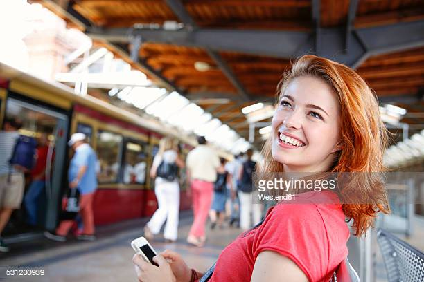 Germany, Berlin, Young woman using smart phone at train station