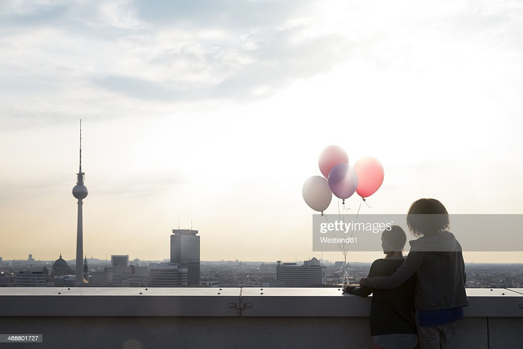 Germany, Berlin, Young women on rooftop terrace, holding balloons