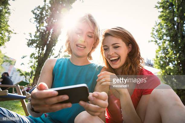 Germany, Berlin, Young women using smart phone in park