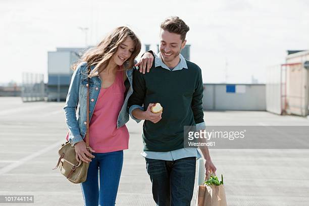 Germany, Berling, Young couple walking on empty parking level, looking down, portrait