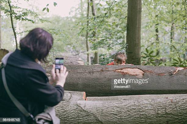 Germany, Bielefeld, mother taking picture of boy behind log in forest
