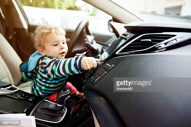 Germany, Bonn, Baby boy turning knob in car