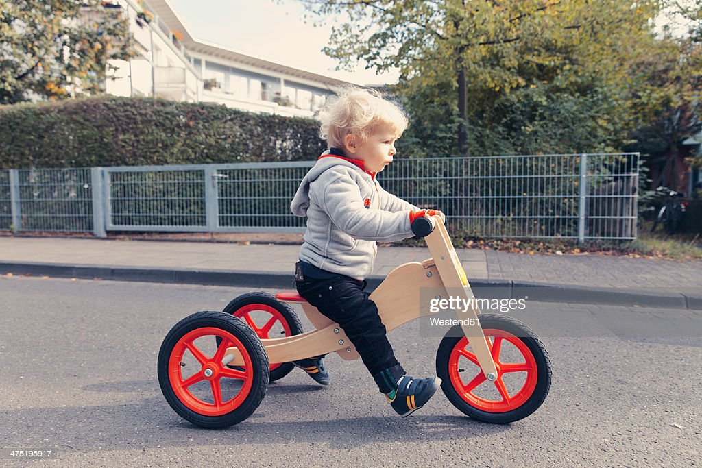Germany, Bonn, Little boy with wood tricycle