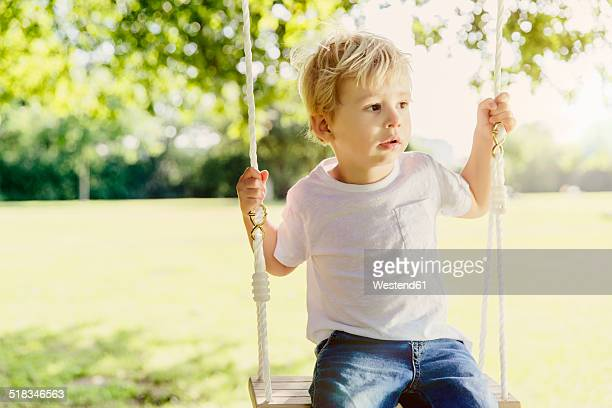 Germany, Bonn, Male toddler sitting on swing under tree in nature, looking away