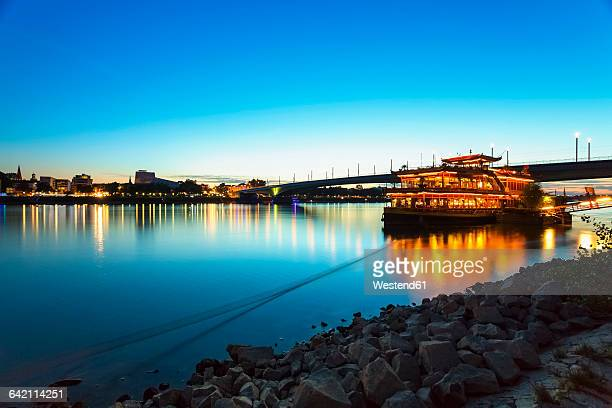 Germany, Bonn, view to Rhine river with lighted restaurant ship