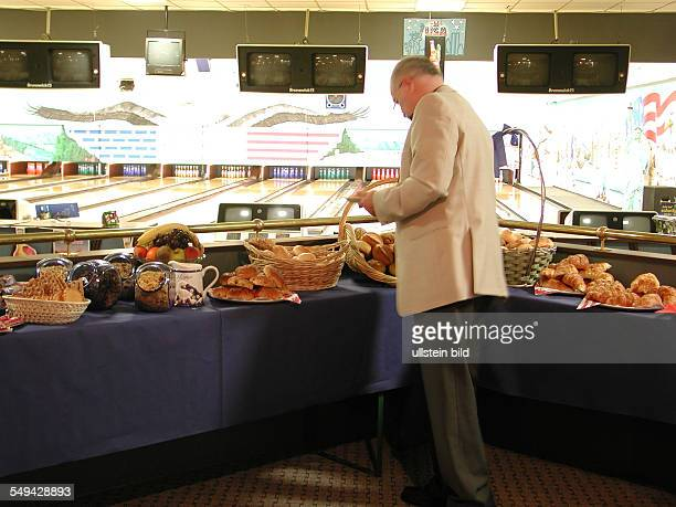 Bowling alley A man helping himself on the breakfast buffet
