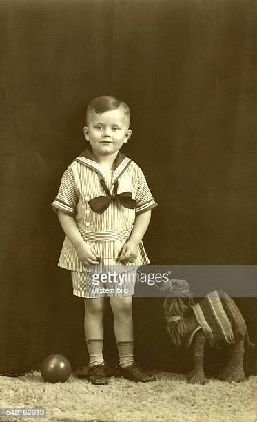 Germany boy in a sailor suit with toy camel about 1926