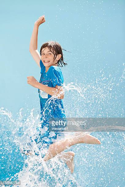 Germany, Boy jumping in splash of water against blue background