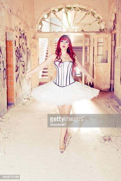 Germany, Brandenburg, Beelitz, woman with red hair and ballerina dress standing in destroyed old house